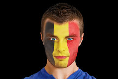 Composite image of serious young beligan fan with facepaint Royalty Free Stock Image