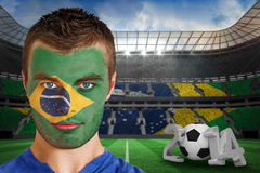 Composite image of serious young brasil fan with face paint Royalty Free Stock Image