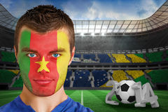 Composite image of serious young cameroon fan with face paint Royalty Free Stock Photography