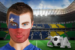Composite image of serious young chile fan with face paint Royalty Free Stock Images