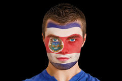 Composite image of serious young costa rica fan with facepaint Stock Photo