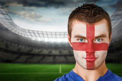Composite image of serious young england fan with face paint Royalty Free Stock Photo