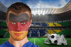 Composite image of serious young german fan with face paint Stock Images
