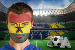 Composite image of serious young ghana fan with face paint Stock Images