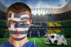 Composite image of serious young greece fan with face paint Royalty Free Stock Image