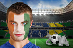 Composite image of serious young ivory coast fan with face paint Royalty Free Stock Images
