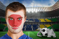 Composite image of serious young japan fan with face paint Stock Images