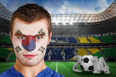 Composite image of serious young korea fan with face paint Royalty Free Stock Photo
