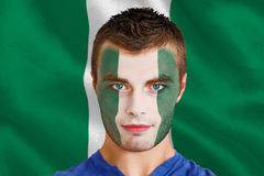 Composite image of serious young nigeria fan with facepaint Stock Photography