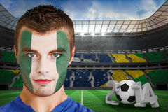 Composite image of serious young russia fan with face paint Stock Image
