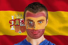 Composite image of serious young spain fan with facepaint Royalty Free Stock Image