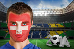 Composite image of serious young switzerland fan with facepaint Royalty Free Stock Images