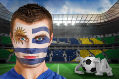 Composite image of serious young uruguay fan with facepaint Royalty Free Stock Images