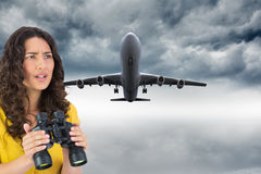Composite image of serious young woman holding binoculars Royalty Free Stock Images
