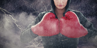 Composite image of serious young woman in red boxing gloves and black hood Stock Images