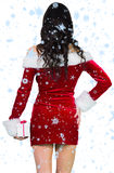 Composite image of sexy girl in santa outfit holding gift Stock Photography