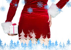 Composite image of sexy girl in santa outfit holding gift Royalty Free Stock Photography