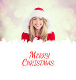 Composite image of sexy santa girl holding gift Stock Images