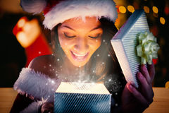 Composite image of sexy santa girl opening gift Royalty Free Stock Photography