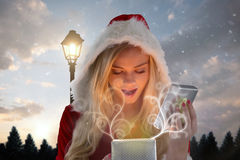 Composite image of sexy santa girl opening gift Stock Photo