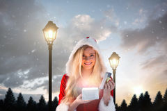 Composite image of sexy santa girl opening gift Stock Image