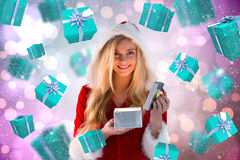 Composite image of sexy santa girl opening gift Royalty Free Stock Photos