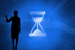 Composite image of shiny hourglass on blue background Royalty Free Stock Photos