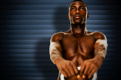 Composite image of shirtless fit young man lifting kettle bell. Shirtless fit young man lifting kettle bell against grey shutters Royalty Free Stock Image