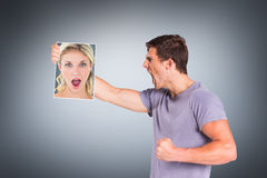 Composite image of shocked blonde holding a sheet of paper Royalty Free Stock Image