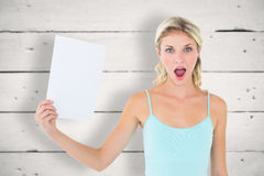 Composite image of shocked blonde holding a sheet of paper Stock Photos