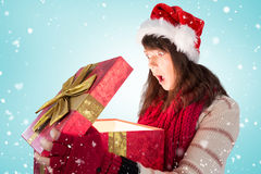 Composite image of shocked festive brunette opening a gift Stock Images
