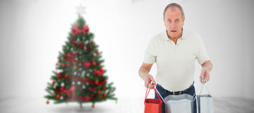 Composite image of shocked man holding shopping bags Stock Photography