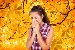 Composite image of sick blonde woman sneezing in a tissue. Sick blonde woman sneezing in a tissue against branches and autumnal leaves Stock Photography