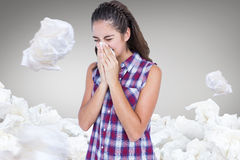 Composite image of sick blonde woman sneezing in a tissue. Sick blonde woman sneezing in a tissue against grey vignette Stock Image