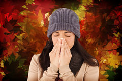 Composite image of sick brunette blowing her nose. Sick brunette blowing her nose against autumnal leaf pattern in warm tones Stock Photo