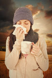 Composite image of sick brunette blowing her nose while holding a mug Stock Photos