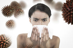 Composite image of sick gorgeous model blowing her nose. Sick gorgeous model blowing her nose against virus stock photos