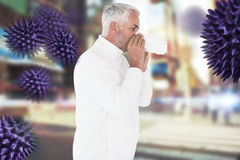 Composite image of sick man in winter fashion sneezing. Sick man in winter fashion sneezing against blurred new york street stock photos