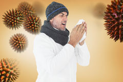 Composite image of sick man in winter fashion sneezing Royalty Free Stock Photography