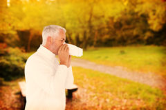 Composite image of sick man in winter fashion sneezing Royalty Free Stock Images