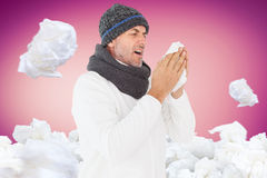 Composite image of sick man in winter fashion sneezing Stock Image