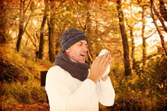 Composite image of sick man in winter fashion sneezing Stock Photos