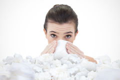 Composite image of sick natural brown haired model sneezing in a tissue Royalty Free Stock Photo
