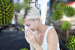 Composite image of sick woman blowing her nose. Sick woman blowing her nose against blurry new york street royalty free stock photo