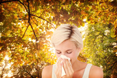 Composite image of sick woman blowing her nose Stock Image
