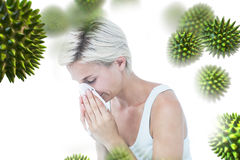 Composite image of sick woman blowing her nose. Sick woman blowing her nose against virus stock images