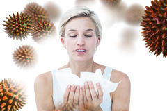 Composite image of sick woman holding tissues. Sick woman holding tissues against virus royalty free stock photo