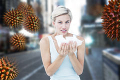 Composite image of sick woman holding tissues looking at camera. Sick woman holding tissues looking at camera against blurry new york street royalty free stock images