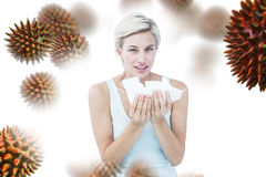 Composite image of sick woman holding tissues looking at camera. Sick woman holding tissues looking at camera against virus stock images