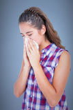 Composite image of sick woman sneezing in a tissue Stock Images